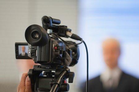 Photo pour Conférence de presse d'entreprise. Caméra vidéo en bref, porte-parole flou - image libre de droit