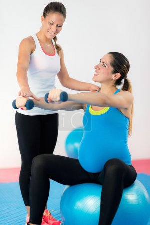 pregnant woman exercising with fitness instructor