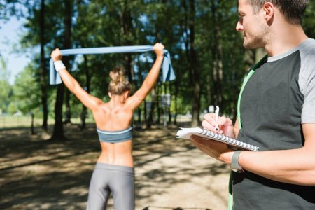 Photo pour Entraîneur personnel avec le client, exercice de musculation de bande, mettant l'accent sur la main et portable - image libre de droit