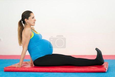 Foto de Mujer embarazada de nueve meses haciendo ejercicios simples en la esterilla - Imagen libre de derechos