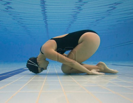 woman in position underwater in pool