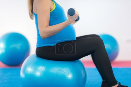 Pregnant woman exercising with dumbbell