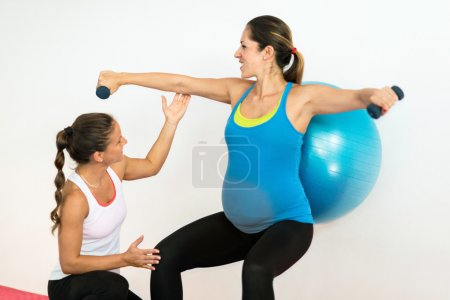 fitness instructor working with pregnant woman