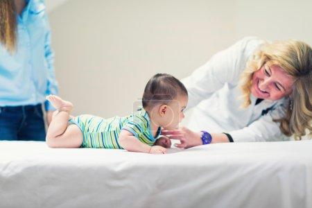 Pediatrician examining cute baby