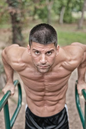 Muscular male athlete on parallel bars