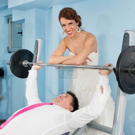 bride adding weight to hardworking groom