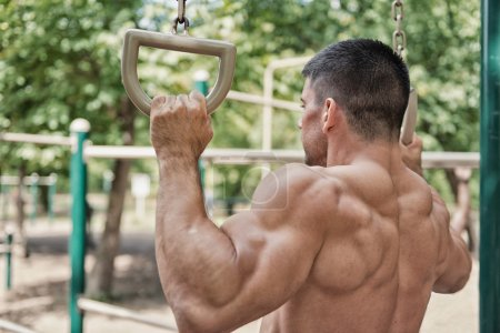 Muscular man exercising on gymnastic rings