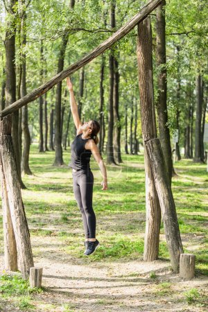 Female athlete jumping on fitness trail