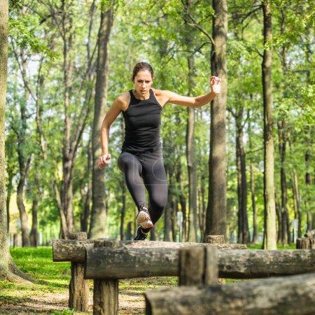 Female athlete crossing hurdles