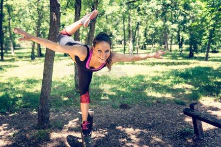 Photo pour Exercice d'équilibrage. jeune femme exerçant dans le parc - image libre de droit
