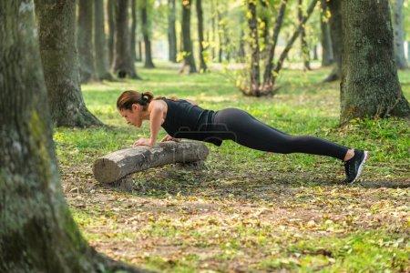 athlete doing push-ups in park