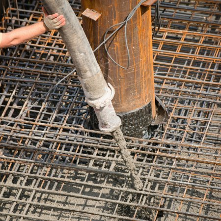 Photo for Worker pouring concrete over iron mesh to create building foundation - Royalty Free Image