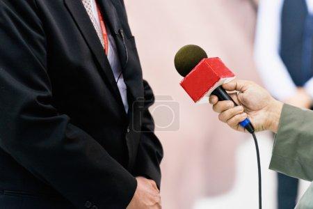 Photo pour Journaliste parlant à un politicien avec microphone - image libre de droit