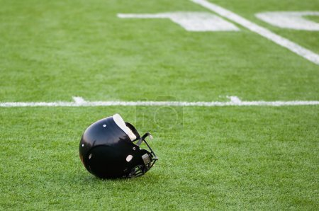 American football helmet on green footbal field...