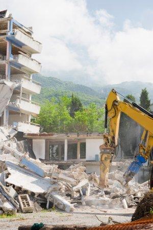 Construction machines demolishing building