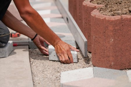 Photo for Manual worker precisely laying street tiles. - Royalty Free Image