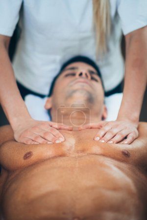 Photo for Physical therapist doing massage of chest. Toned image, selective focus set on chest and hands - Royalty Free Image