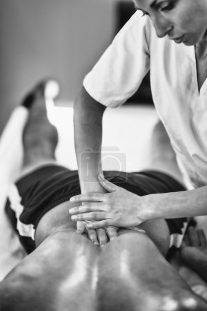 Photo for Physical therapist doing massage of lower back. Black and white photo, selective focus - Royalty Free Image