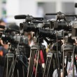 Row of TV cameras lined up, covering public event...