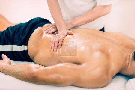 Photo for Physical therapist doing massage of lower back. Toned image, selective focus - Royalty Free Image