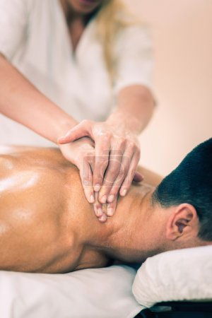 Photo for Physical therapist doing massage of neck. Toned image, selective focus set on chest and hands - Royalty Free Image