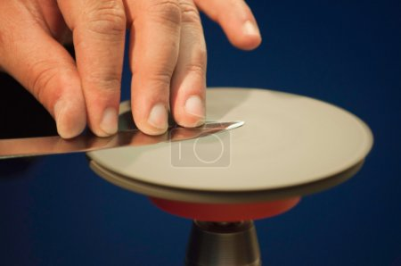 Photo for Close-up partial view of person sharpening knife on the spinning disk - Royalty Free Image