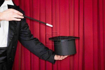 Photo pour Magicien sur scène faisant un tour avec chapeau haut de forme - image libre de droit