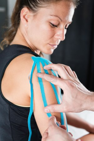 therapist placing kinesio tape on shoulder
