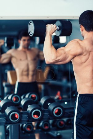 Body building champion exercising in front of mirror