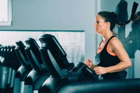 Photo for Female athlete running on treadmill in modern gym. - Royalty Free Image