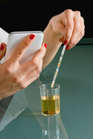 Woman testing urine with reagent paper