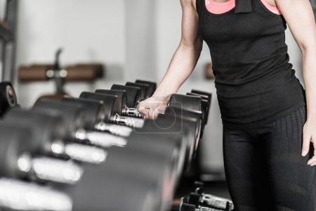 Woman taking dumbbell in health club