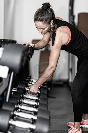 Woman taking dumbbell