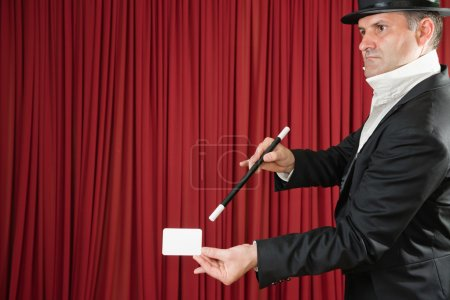 Magician on stage doing trick with card