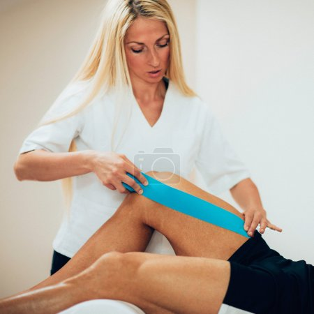Physical therapist placing kinesio tape