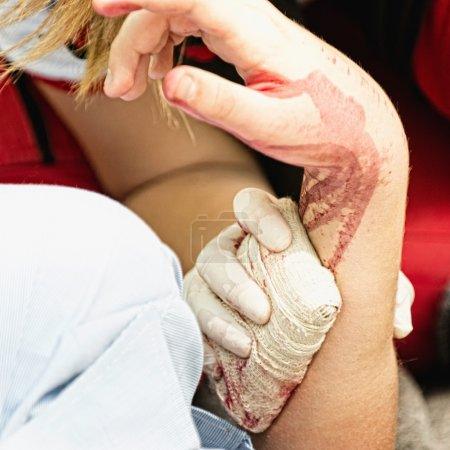 Photo for Paramedic applying bandage to arm of a victim at disaster site - Royalty Free Image
