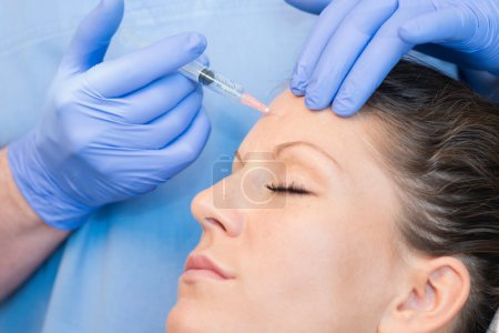 Botox injection on woman forehead
