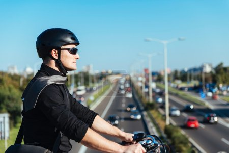 Photo for Businessman on electric bicycle driving on bridge - Royalty Free Image