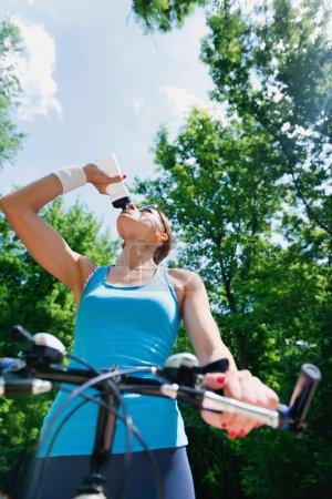 female biker takes water break