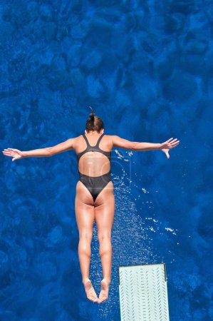 Female springboard diving competitor in air