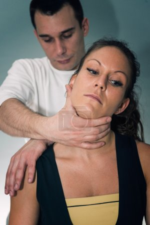 chiropractor examining female neck