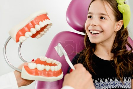 ittle girl learning  brush teeth