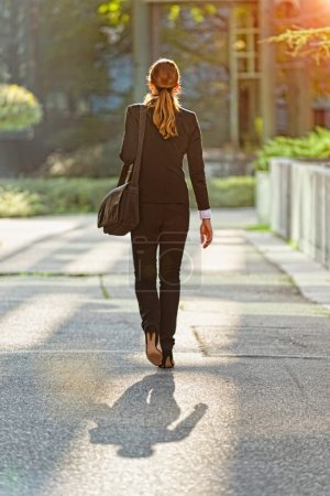 businesswoman going to work in green city