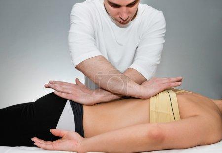 Photo pour Mâle ostéopathe travaillant sur le dos du patient - image libre de droit