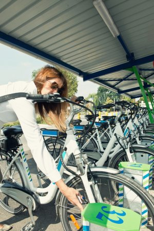 female commuter on  bicycle sharing station