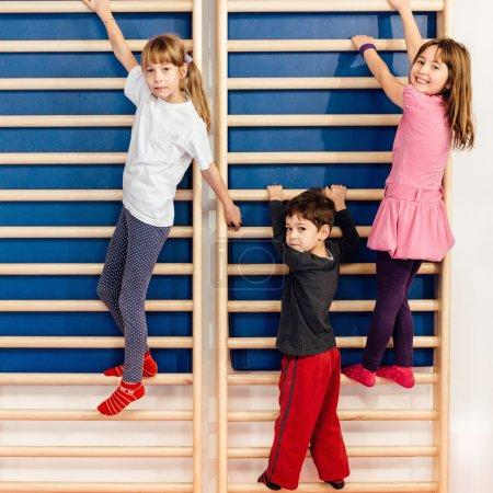 children climbing on wall bars