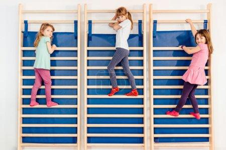 little girls climbing on wall bars