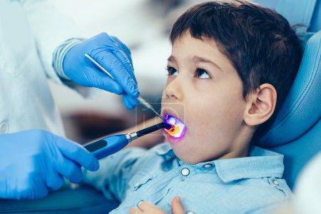 Dentist drying boy tooth