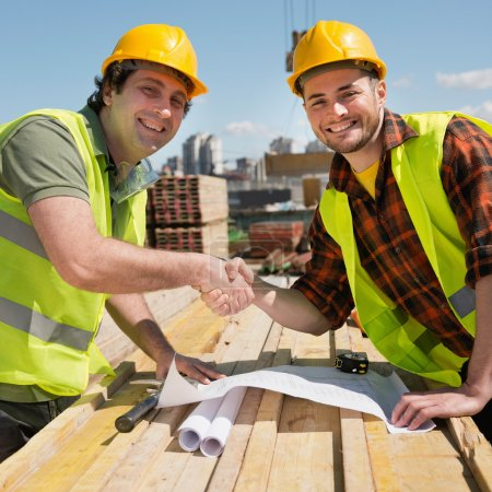 Construction workers shaking hands on construction...