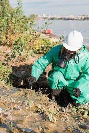 Environmentalist  taking sample of soil